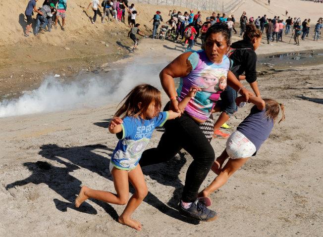 美墨邊境一名無證母親拉著孩子,躲避催淚瓦斯的攻擊。(路透)