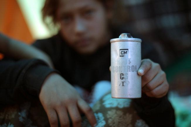 墨西哥提璜納市一名宏都拉斯無證青年撿起一個催淚瓦斯罐,上頭寫著「暴亂控制」。(路透)
