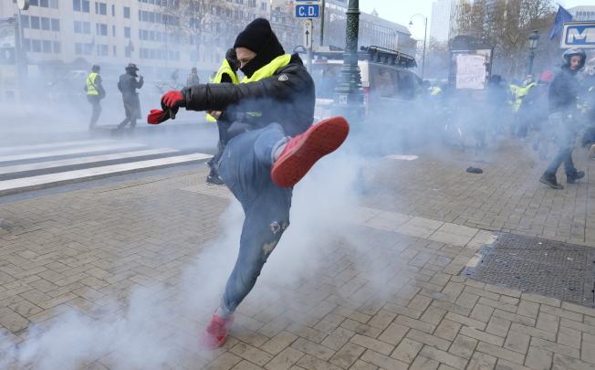 抗議者一腳踢走催淚瓦斯罐。(歐新社)