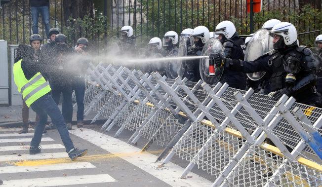 比利時警方以催淚瓦斯罐攻擊一名「黃背心」抗議男子。(路透)