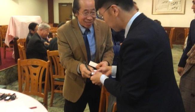 多位傳統僑社僑領與簡槙男(右)交換名片。(記者謝雨珊/攝影)