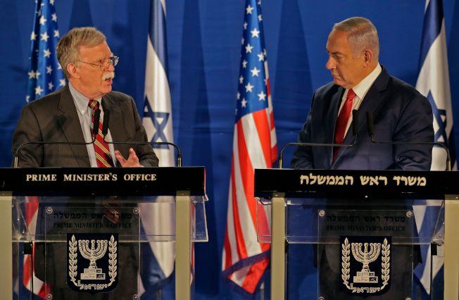 白宮國家安全顧問波頓(左)6日在訪問以色列時表示,美軍自敘利亞撤軍之事,暫緩執行。圖為波頓與以色列總理內唐亞胡的記者會。(Getty Imags)