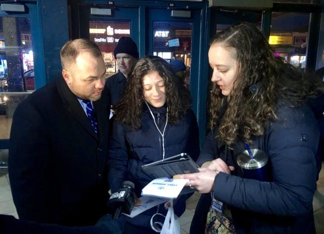 張晟(左一)幫助乘客填寫調查問卷。(記者朱蕾/攝影)