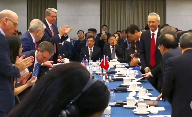 美中经贸的第一轮谈判7日在北京举行,由两国副部级官员参加。主管金融事务的中国副总理刘鹤(右立者)在会中突然意外现身,引起一阵骚动。这帧由不知名人士所摄并流出照片,显示图左侧的美方代表起立鼓掌表示欢迎。