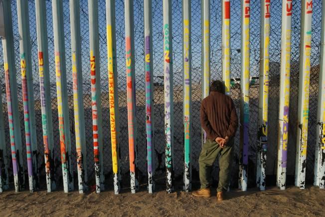 一名男子從墨西哥提璜納透過鐵欄杆和鐵絲網間隙,望向美國。(Getty Images)