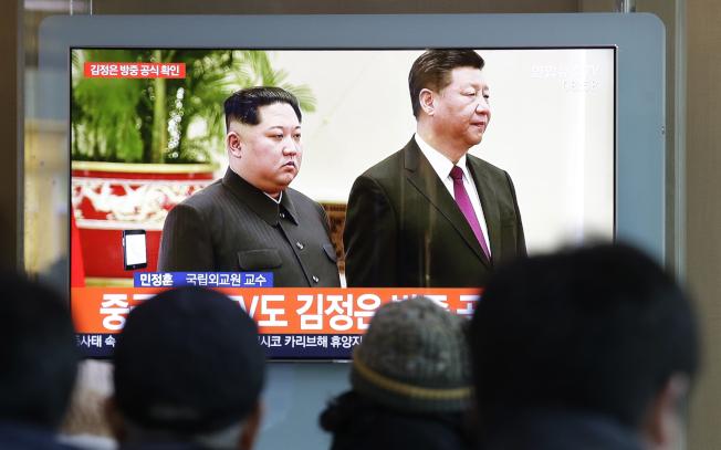 南韓民眾8日在首爾火車站觀看新聞報導北韓領導人金正恩(左)訪問中國國家主席習近平(右)。(美聯社)