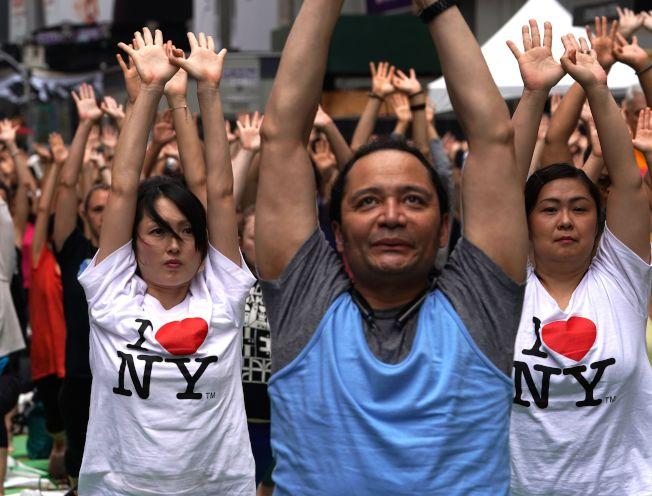 紐約市長白思豪推全民健保,納入紐約市60萬低收入和無證移民。圖為穿著「我愛紐約」的市民去年夏天在時報廣場參加全民瑜伽日活動。(Getty Images)