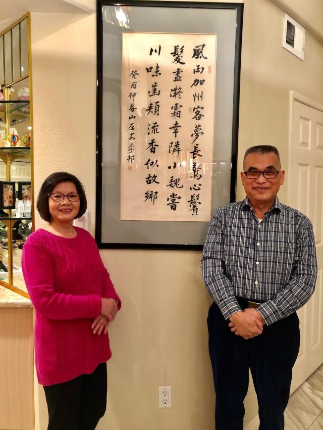 小魏夫妇与书法家安季邦早年赠予他的字画合影。(记者胡清扬/摄影)
