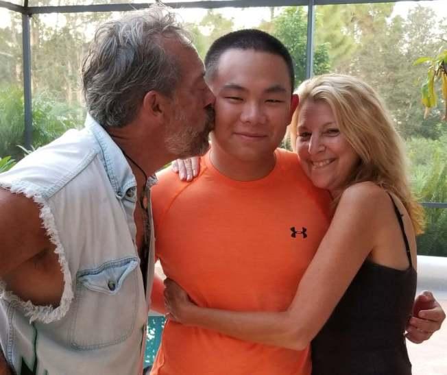新华•梅森伯格生前和养父母Mitch、Shannon。(Mitch Mesenburg脸书)