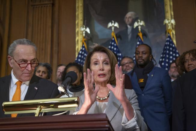 代表民主黨進入白宮協商的眾院議長波洛西(右)與參院少數黨領袖舒默,重申民主黨願意重開政府立場。後為受政府關閉影響的聯邦員工。(Getty Images)