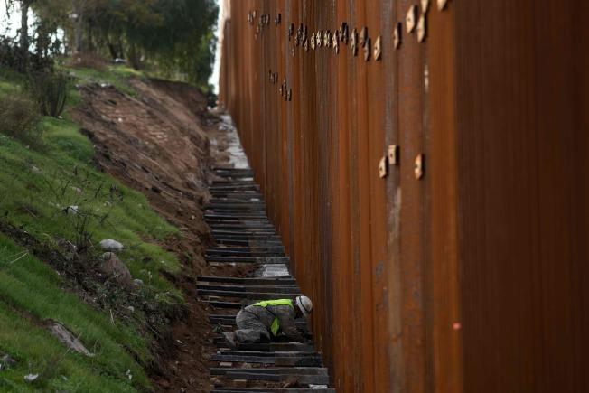 川普高唱興建邊牆時,一名建築工正在美墨邊界檢查邊界圍籬安全。(Getty Images)