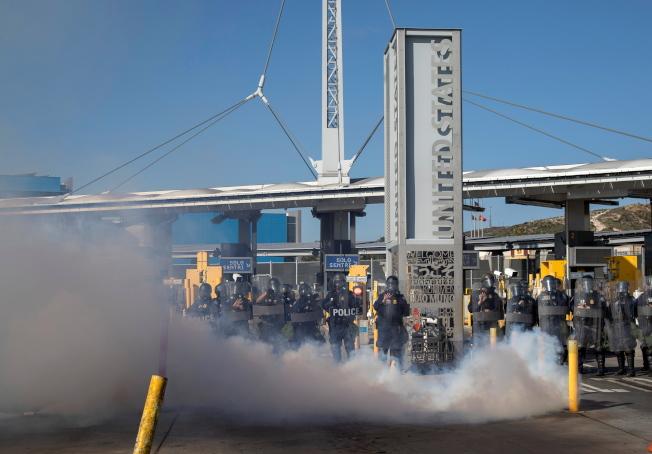 川普總統赴德州視察南部邊牆,南加州聖西德羅入境口岸也舉行「運作準備演習」,邊境巡邏隊一面施放煙霧,同時全副武裝準備應付假想會湧進美國的成群難民。(歐新社)