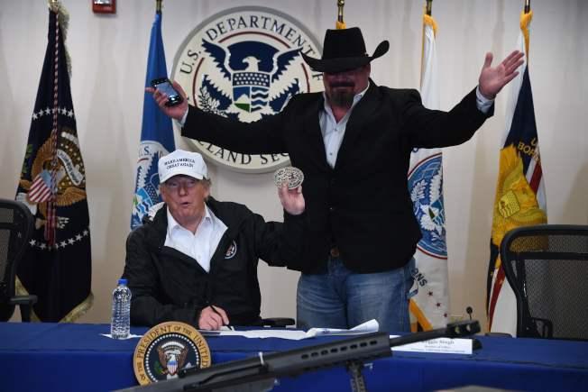 川普總統視察美墨交界的德州格蘭德河谷,在麥克阿倫分隊告訴邊界巡邏隊員準備應付邊界危機,並接受邊界民防隊員送給他的一個皮帶扣。(Getty Images)