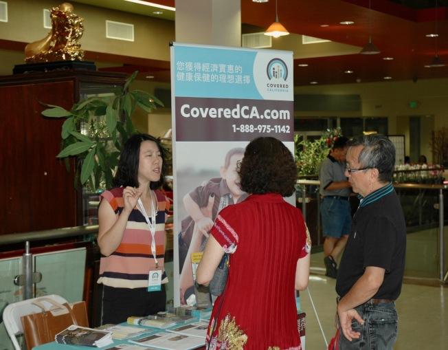 工作人員(左)向華人民眾介紹加州全保醫療保險計畫。(記者丁曙/攝影)