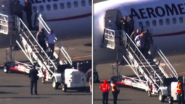 兩名被拘的乘客,被帶下機。(電視新聞截圖)