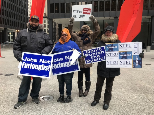 多位聯邦職工舉著「要工作不要無薪假」等標語,在芝加哥聯邦廣場抗議。(特派員黃惠玲╱攝影)