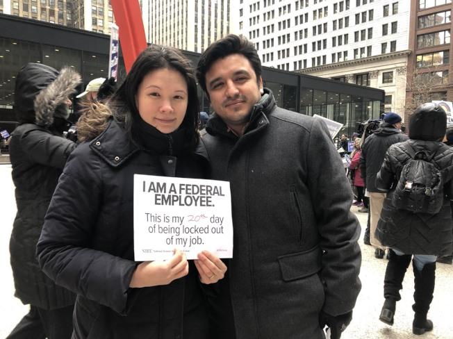 因聯邦政府關門拿不到薪水的聯邦雇員盧玲玲(左)和新婚的丈夫盧漢士(右)在芝加哥參加抗議活動。(特派員黃惠玲╱攝影)