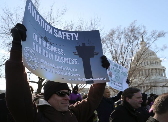 聯邦政府部分關閉已進入第三周,聯邦員工急著要回去工作,一名示威者在國會前面舉起標語,要求議員重視飛航安全。(Getty Images)