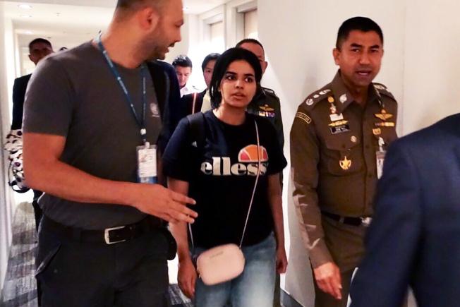 沙烏地阿拉伯少女奎農(中)7日在泰國移民署署長蘇拉切(右)陪同下,離開曼谷機場旅館。Getty Images