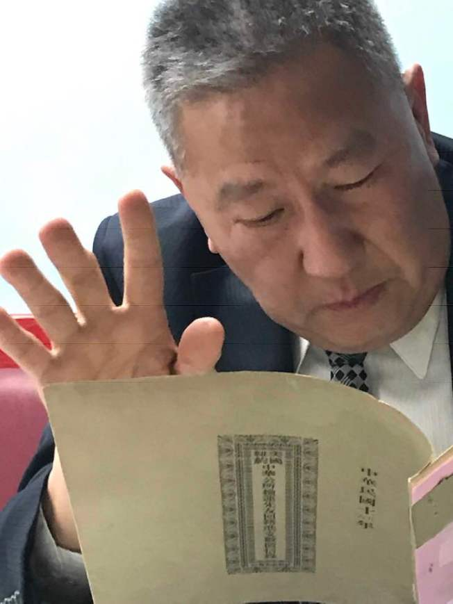 紐約中華公所主席伍銳賢讀「落葉歸根」徵信錄。(熊傳慧/攝影)