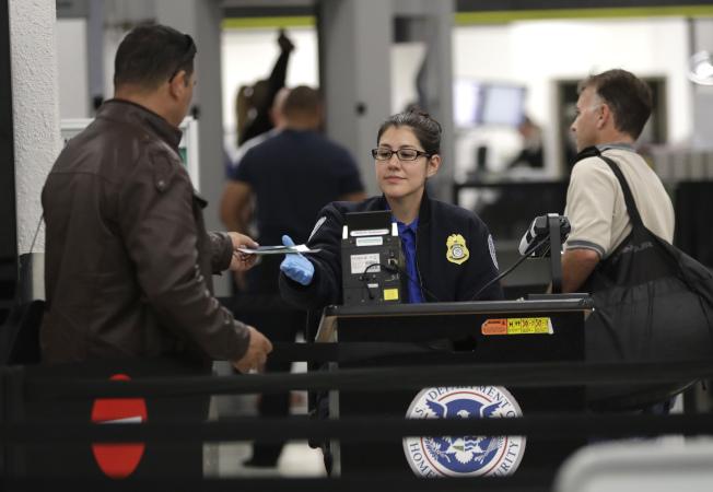 政府部分關門,部分機場的TSA員工拒絕工作,迫使佛州邁阿密機場關閉一座航站樓。圖為邁阿密機場TSA員工正進行證照查檢。(美聯社)