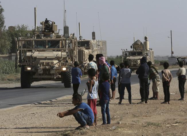 配合川普總統的撤軍決定,美軍已開始從敘利亞撤出部分裝備。圖為2017年7月美軍車輛行駛在敘利亞東北部的公路。(美聯社)