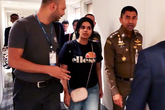 沙烏地阿拉伯18歲少女艾奎農(中)離家逃往國外,獲得加拿大庇護,圖為她在泰國曼谷機場搭機轉往加拿大。(Getty Images)