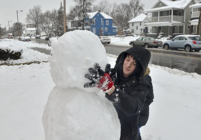 印第安納州一名居民則堆了一個比自己還高的雪人。(美聯社)