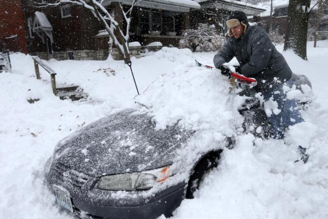 今年第一場大風雪橫掃美中地區,在部分地區降下18吋的積雪。圖為聖路易一名居民12日奮力把遭大雪深埋的車子挖出。(美聯社)