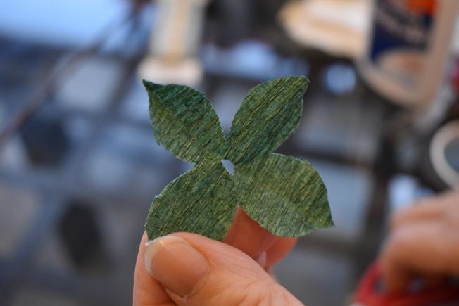 花托用正方形綠皺紋紙沿對角線對摺三次,開口朝上剪成半月形,打開後成為十字形狀剪紙,中間留一個洞讓牡丹花莖穿過。(記者顏嘉瑩/攝影)