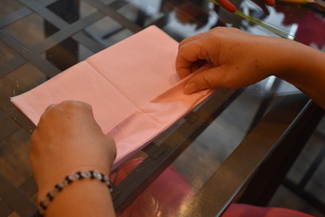 將剪成同樣大小的禮物紙疊在一起,5公分一摺,正反摺成長條摺扇狀。(記者顏嘉瑩/攝影)