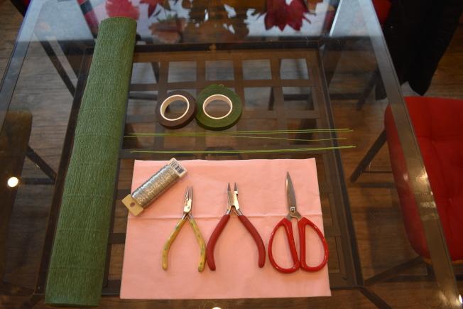 製作牡丹花盆的材料需要禮物紙、花藝用綠鐵絲粗細數根、細鐵絲、綠色皺紋紙、綠色和咖啡色花藝膠帶、白膠等。(記者顏嘉瑩/攝影)