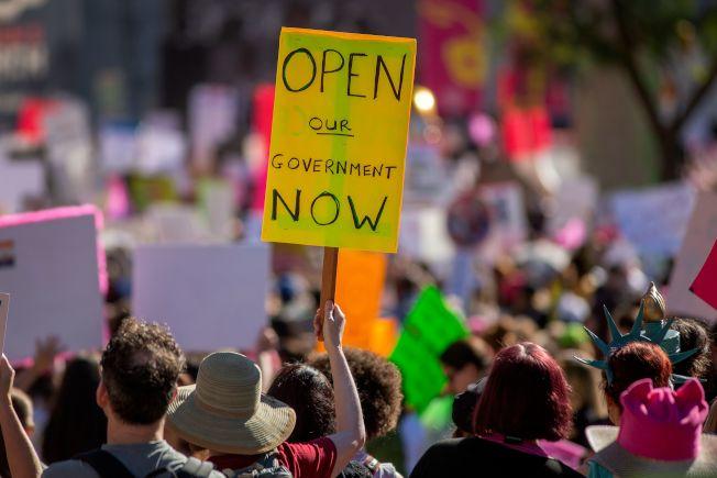 在全美女性大遊行隊伍裡,有人舉牌要求「立刻重開政府」。(Getty Images)