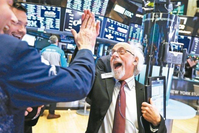股市大漲,圖赫曼興奮地與同事擊掌慶祝。(美聯社)