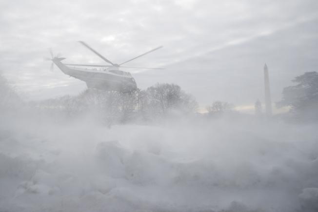川普總統搭乘「陸戰隊1號」直升機離開白宮南草坪,吹起積雪,一片混沌。(美聯社)