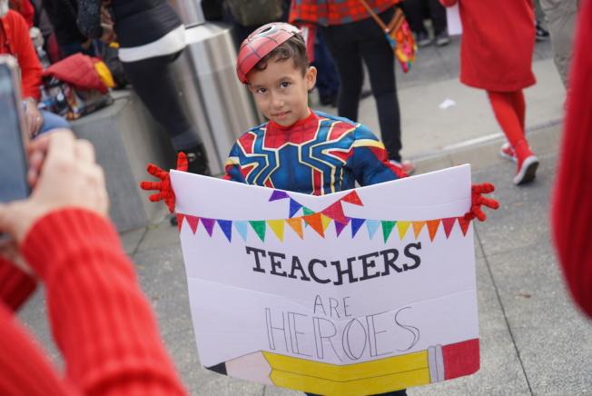 孩子举起手牌「老师是英雄」。(记者王千惠/摄影)