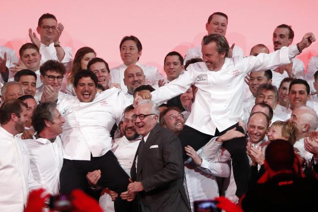 今年法國米其林指南揭曉,主廚克萊格瑞克(左)和主廚裴狄特(右)被抬起歡呼。(美聯社)