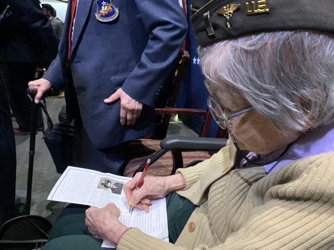 五位華裔二戰老兵在退伍軍人事務部接受表彰,曾在陸軍護士團服役的陳貞潔年過百歲,但思維敏捷,還能書寫自己的中文名。(記者羅曉媛/攝影)