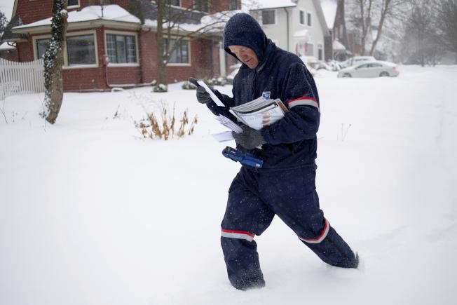 由於嚴寒,中西部十州停止送信。圖為郵差前兩天冒著風雪在密西根州東大湍市送信。(美聯社)