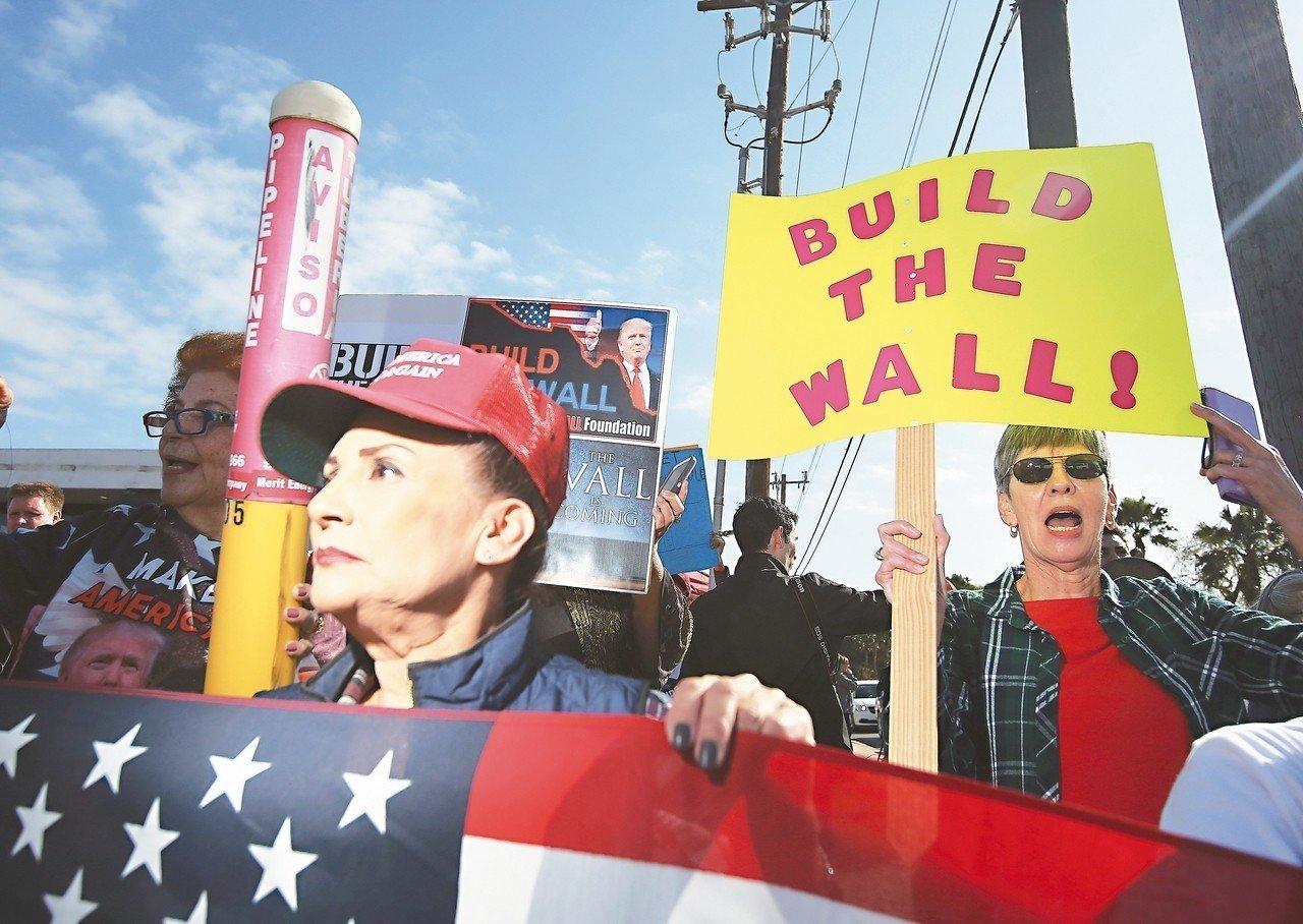 一群美國民眾10日在德州麥艾倫機場高舉國旗和標語,支持美國總統川普築邊界牆。 (美聯社)