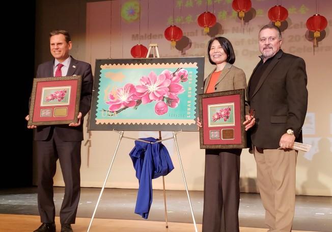 波士頓郵政局長Nick Francescucci (右)公布豬年郵票設計,並贈紀念郵票給摩頓市長Gary Christenson(左),和華夏文協主任洪梅(中)。(記者唐嘉麗/攝影)