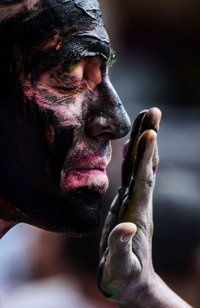 美國白人把臉抹黑,現在被視為對黑人不敬,圖為哥倫比亞黑白嘉年華,一名白人男子在臉上塗抹黑色顏料。(Getty Images)
