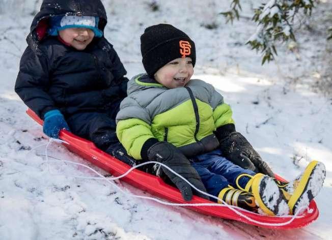 東灣卡斯楚谷5日罕見地下雪,小孩樂不可支,拿著雪撬在山坡上滑雪。(電視新聞截圖)
