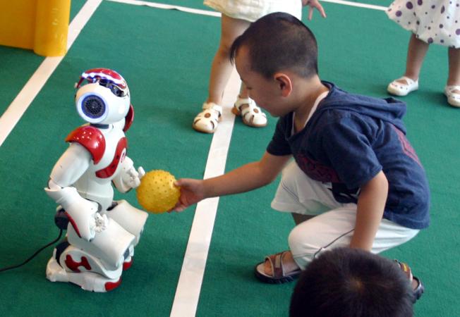 小朋友與機器人互動玩球。(新華社)