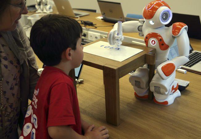 青少年看著機器人寫數學公式。(路透)