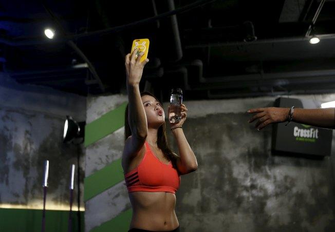 許多人會在健身時自拍記錄自己,圖為南韓健身教練Ray Yang在健身課前自拍。(路透)