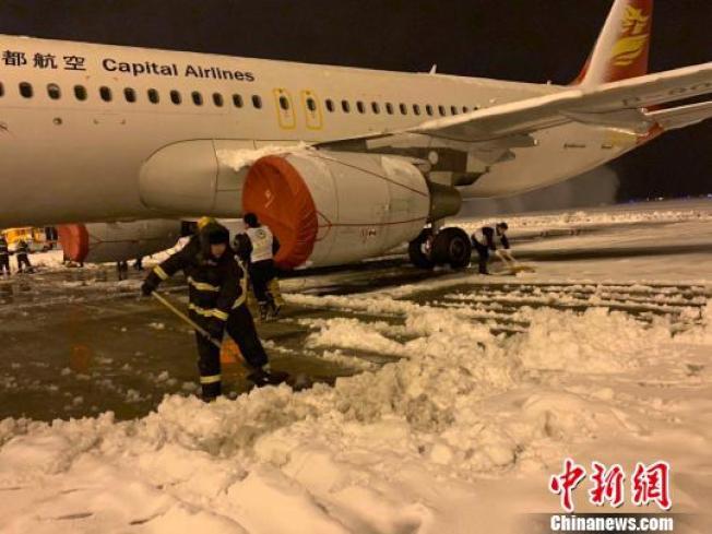 8日晚,大雪紛飛致南京祿口國際機場跑道關閉,機場內在緊張進行掃雪除冰工作。(取材自中新網)