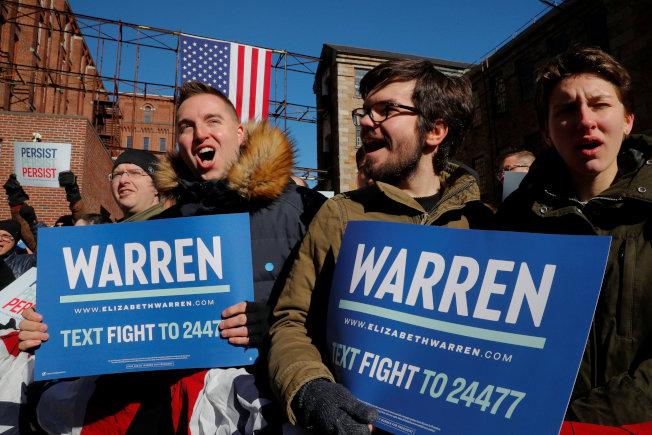 麻州國會參議員華倫宣布參選,角逐2020年民主黨總統提名,圖為支持者在台下舉起競選標語。(路透)