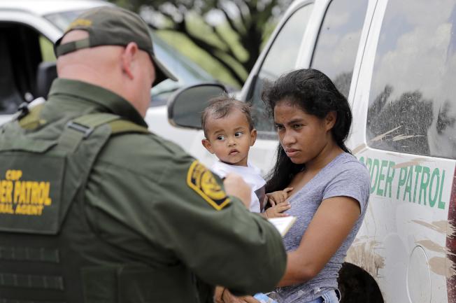 美國邊境巡邏探員在德州麥克阿倫逮捕越界進入美國的一對母子。(美聯社)