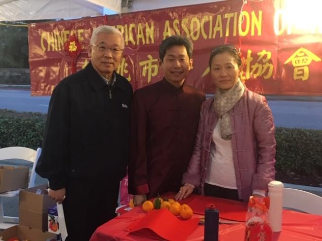 华裔市议员秦振国(中)与核桃市华人协会大年初五新春园游会上为民服务。(记者杨青/摄影)